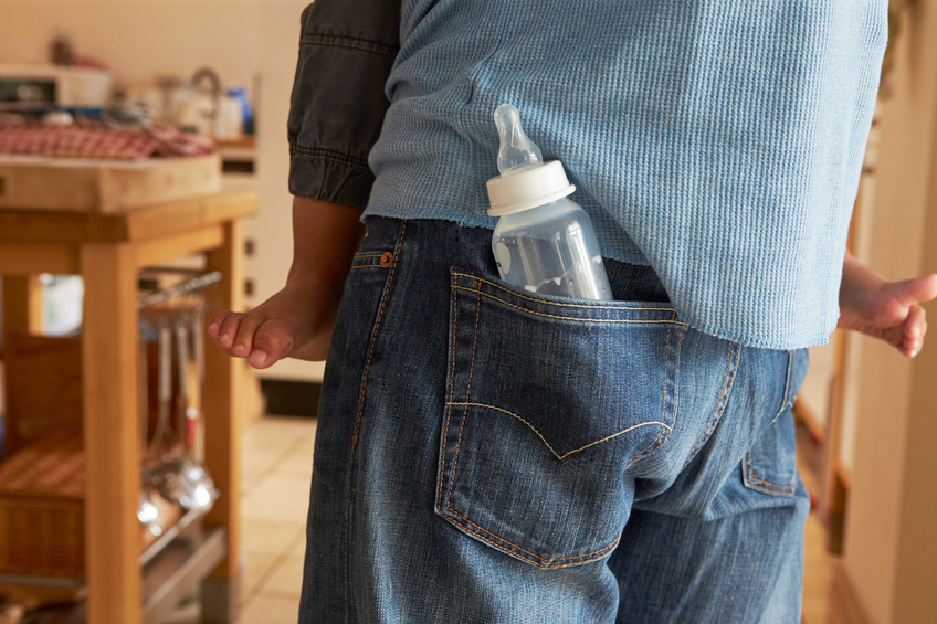 Feeding Bottle In Father's Pocket As He Holds Son
