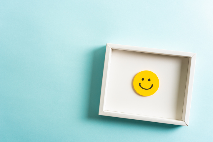 Concept of well-being, well done, feedback, employee recognition award. Happy yellow smiling emoticon face frame hanging on blue background with empty space for text.